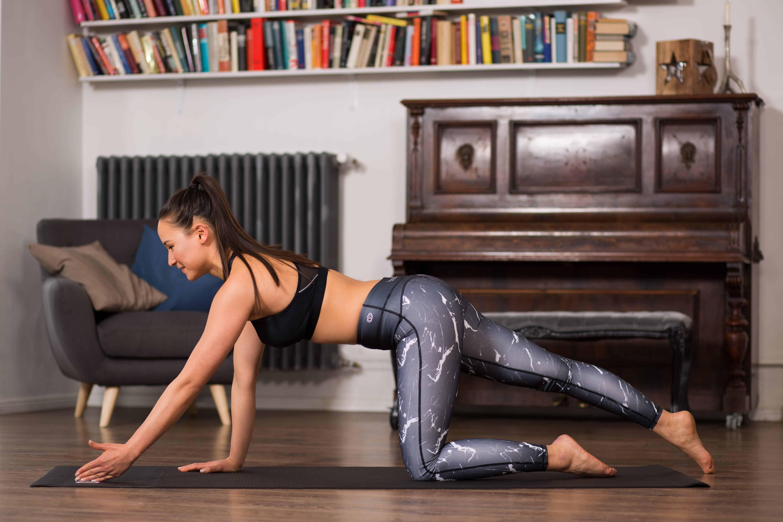 Frau macht Pilates Übung Quadruped