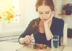Frau stochert lustlos mit Gabel in ihrem Salat