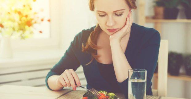 Frau stochert lustlos im Salat