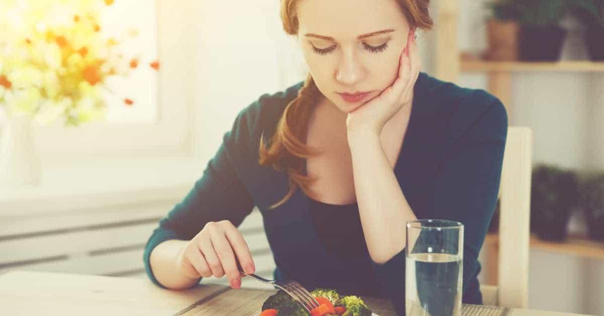 Frau stochtert mit Gabel lustlos in ihrem Salat