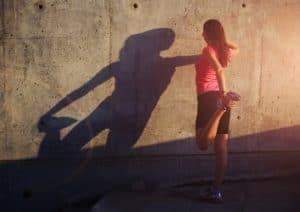 Sportlerin wärmt sich vor dem Training auf vor einer Wand.