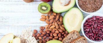 Ein Tisch mit Ballaststoffreichen Lebensmitteln wie Äpfeln, Vollkornprodukte, Bohnen