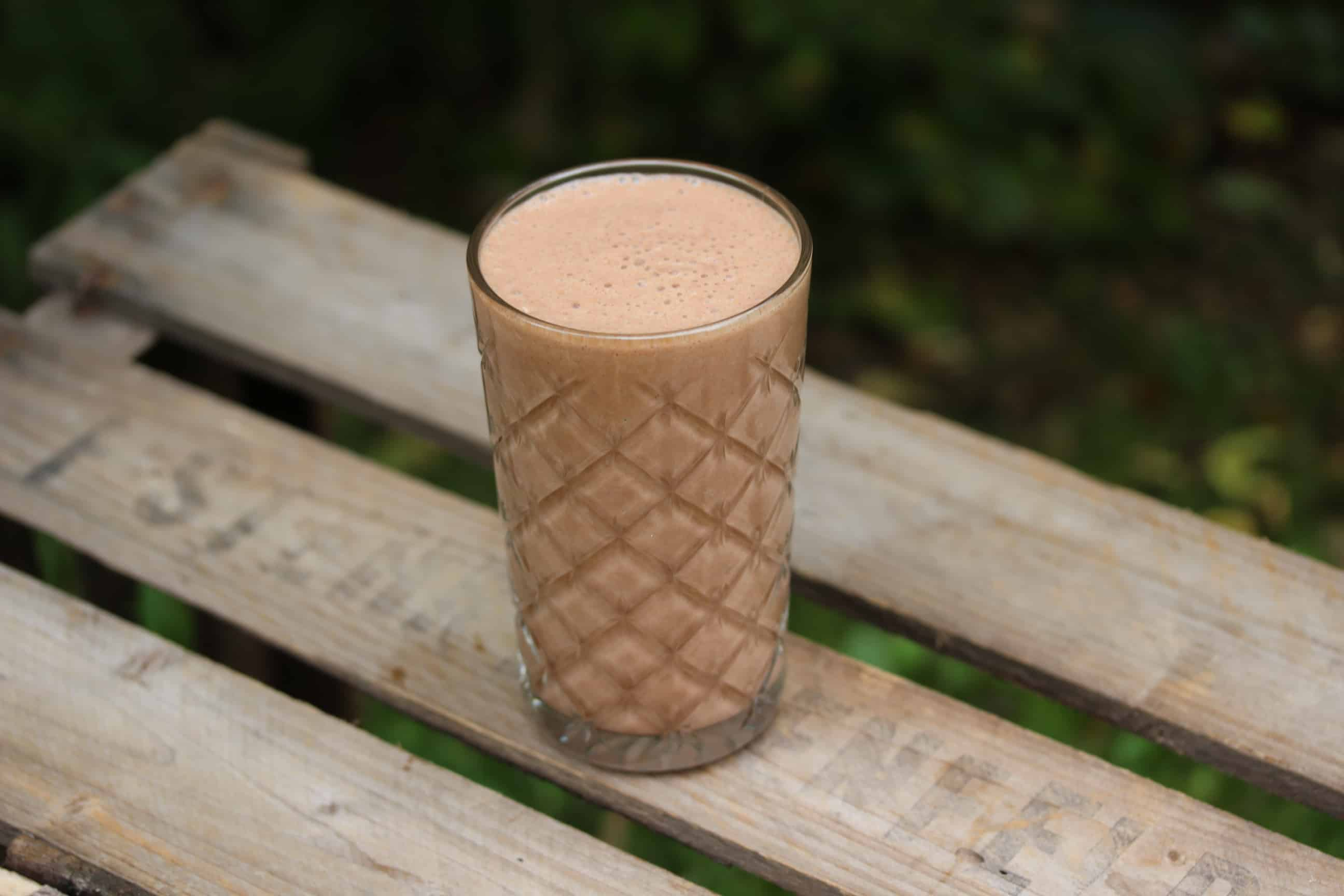 SuperGoodFood Banana-Coconut-Raw Cacao Proteinshake in Glas auf Holztisch