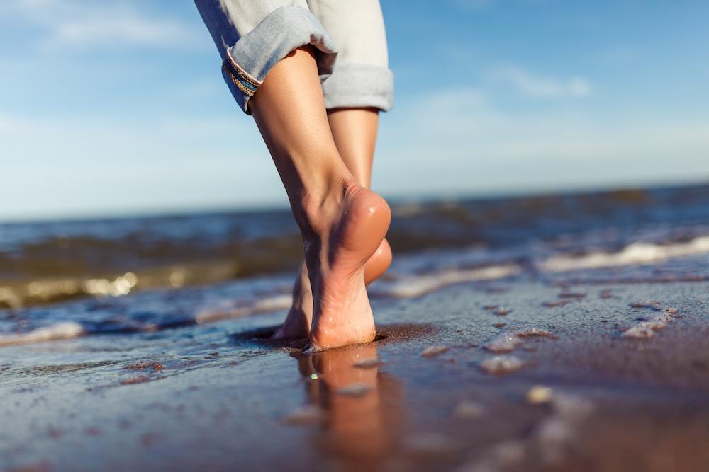 Frau läuft am Strand barfuß durch den Sand, denn barfußlaufen ist gesund