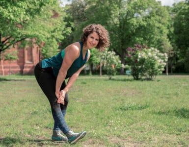 Junge Frau auf einer Raststätte macht Übung Bein Stretch