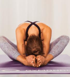 Valerie Junger sitzt im Schneidersitz auf einer lila Trainingsmatte von Gymondo und macht Yin Yoga