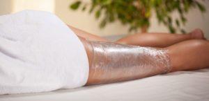 Body Wrapping Behandlung Frau auf Tisch.