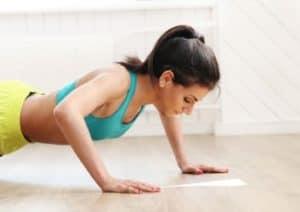 Sportlerin zuhause macht bodyweight zirkeltraining mit Körpergewicht.