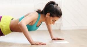 Sportlerin zuhause macht bodyweight zirkeltraining mit Körpergewicht