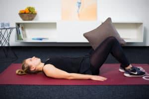 Junge Frau auf Trainingsmatte macht Übungen für den Beckenboden mit Kissen