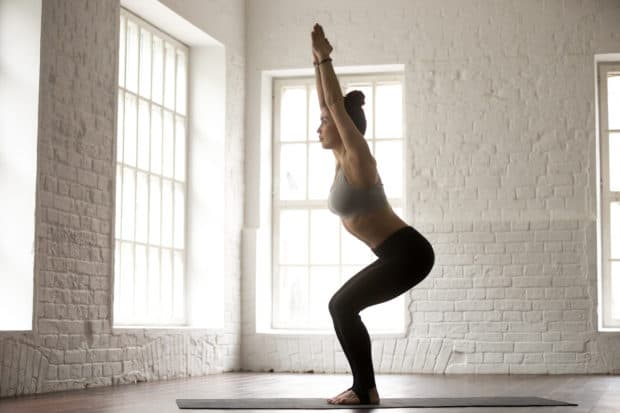 Junge Frau macht Yoga Pose Stuhl