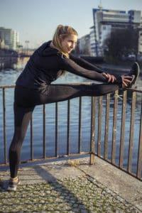 Frau beim Lauftraining in Laufkleidung dehnt sich ein Bein auf ein Geländer gelegt.