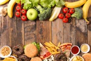 Holztisch oben gesundes Obst und Gemüse unten Fatsfood