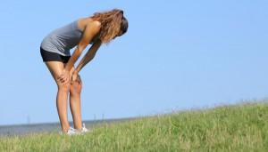 Eine erschöpfte Frau steht auf der Wiese. Beim Sport im Freien macht die Lunge bei Allergikern schnell schlapp.