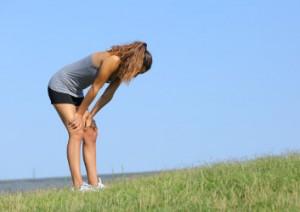 Eine Sportlerin mit Heuschnupfen steht erschöpft auf einer Wiese.