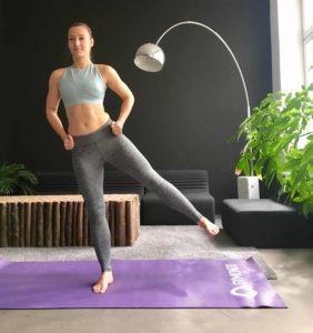 Frau macht Seitliches Beinheben auf lila trainingsmatte