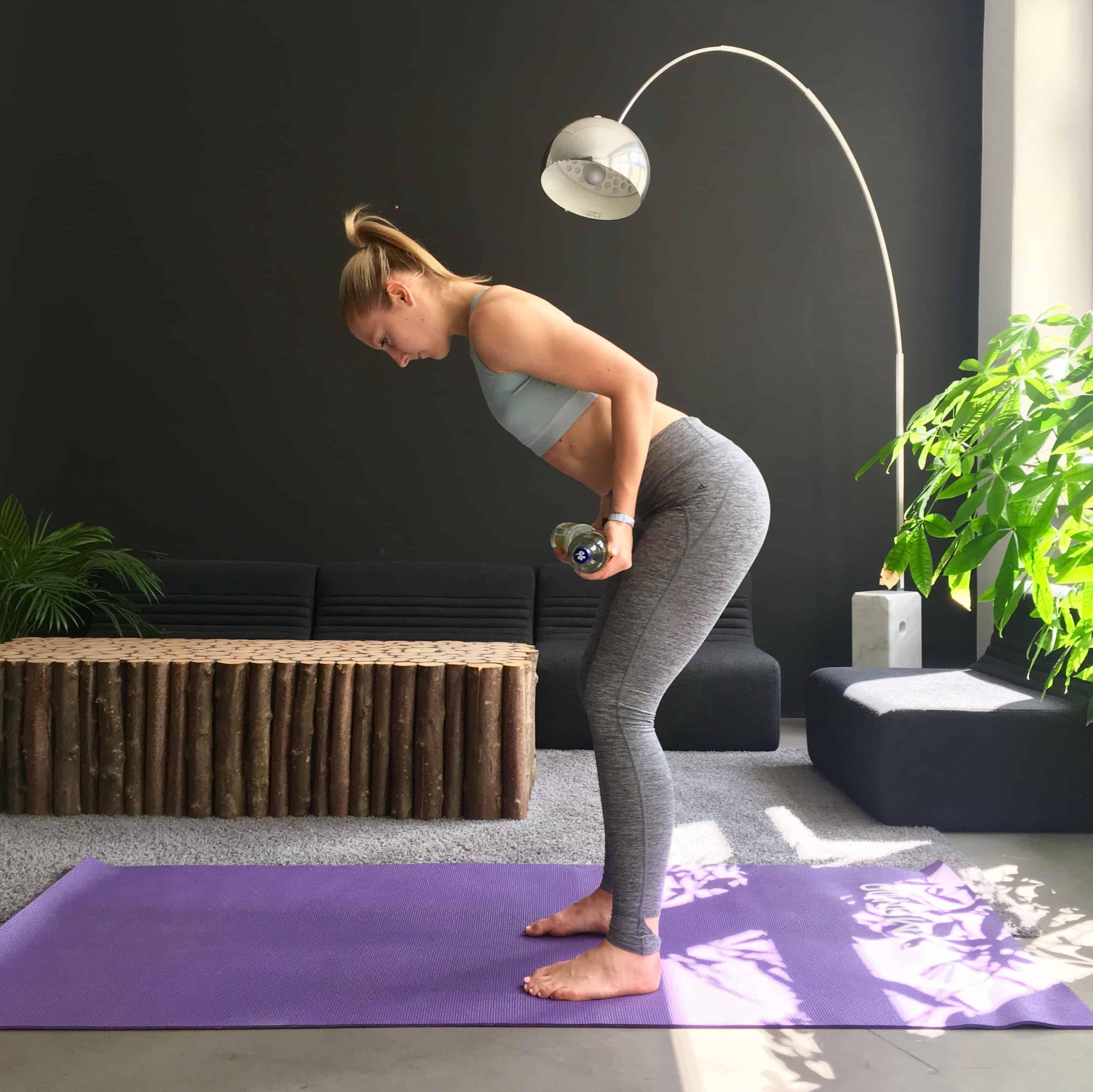 Frau macht Rückenübung rudern mit wasserflaschen