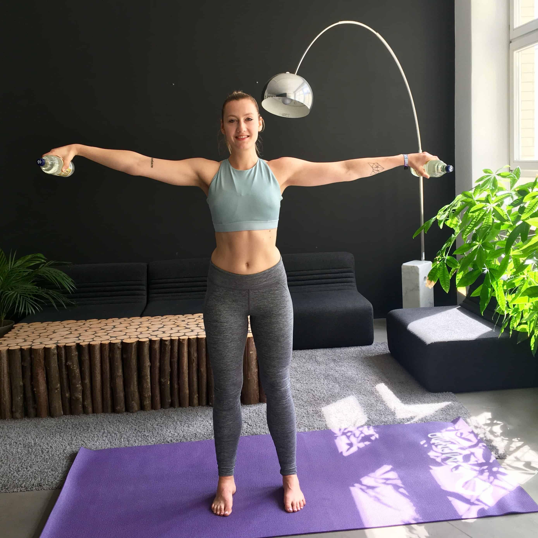 Frau macht seitheben mit wasserflaschen auf lila trainingsmatte