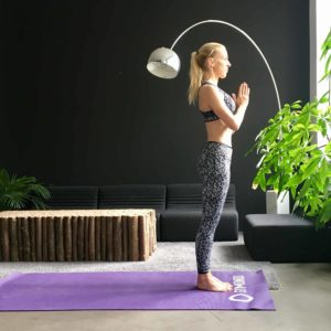 Frau macht Yoga Sonnengruß Berg Pose auf lila Trainingsmatte