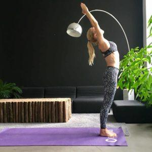 Frau macht Yoga Sonnengruß gestreckter Berg auf lila Trainingsmatte