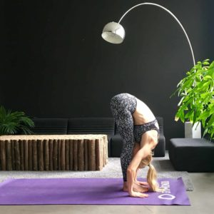 Frau macht Yoga Sonnengruß Vorbeuge auf lila trainingsmatte