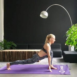Frau macht Yoga Sonnengruß Ausfallschritt auf lila trainingsmatte