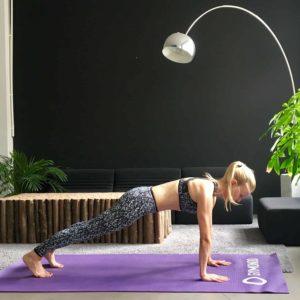 Frau macht Yoga Sonnengruß Brett auf lila Trainingsmatte
