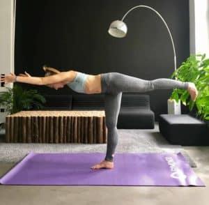Frau macht Standwaage auf lila trainingsmatte