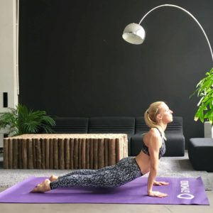 Frau macht Yoga Sonnengruß up dog auf lila trainingsmatte
