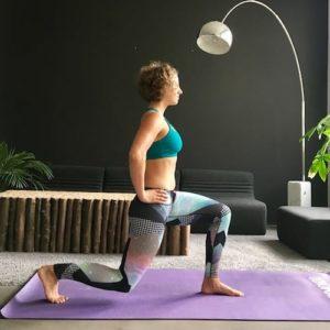 Frau macht Yoga Ausfallschritt auf lila Trainingsmatte