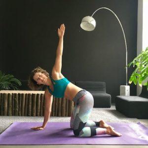 Frau macht Yoga gedrehte katze auf lila Trainingsmatte