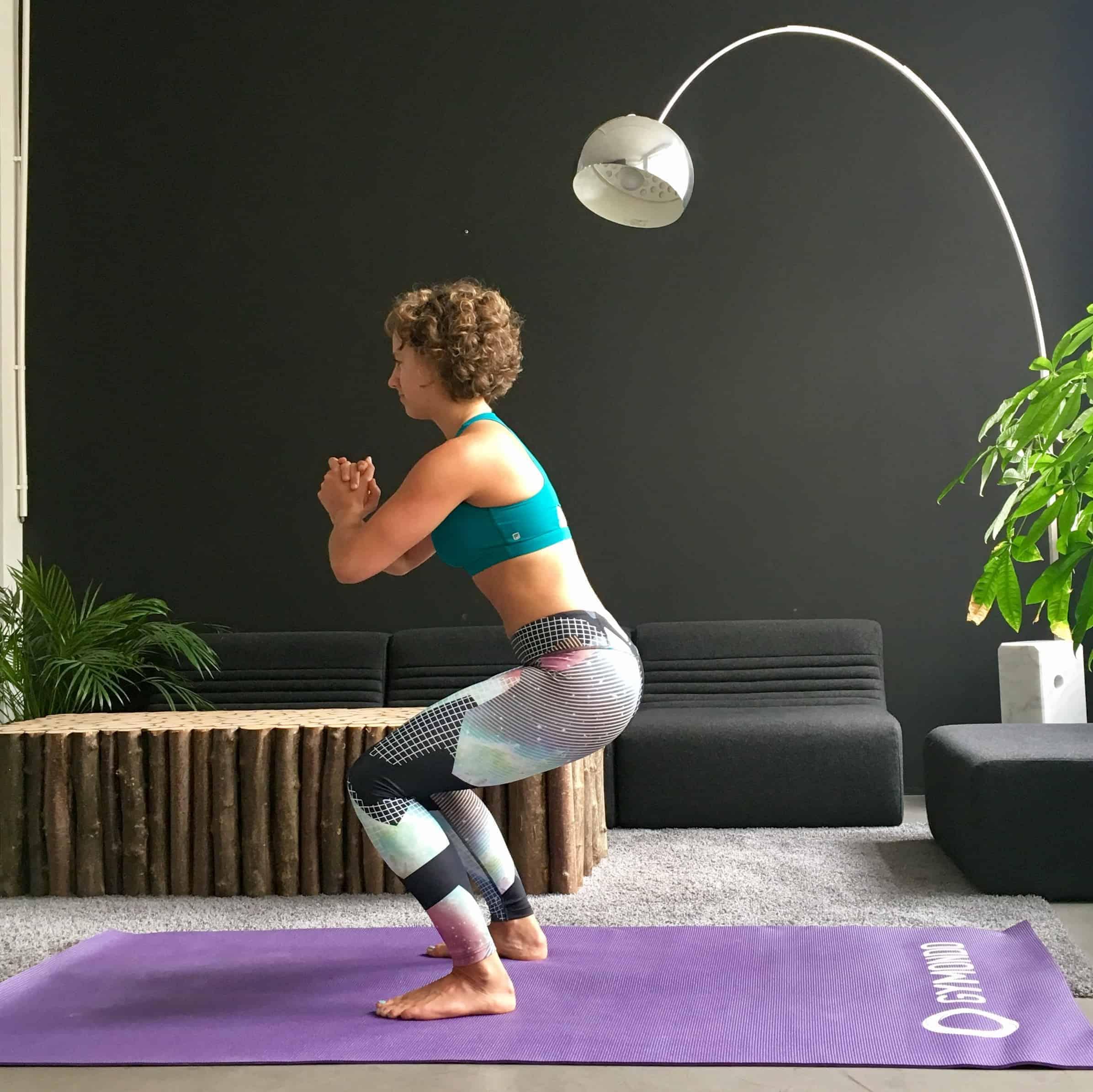 Frau macht Squats auf lila trainingsmatte