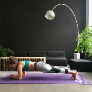 Frau macht Plank auf lila trainingsmatte