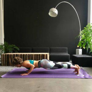 Frau macht Push Ups auf lila trainingsmatte