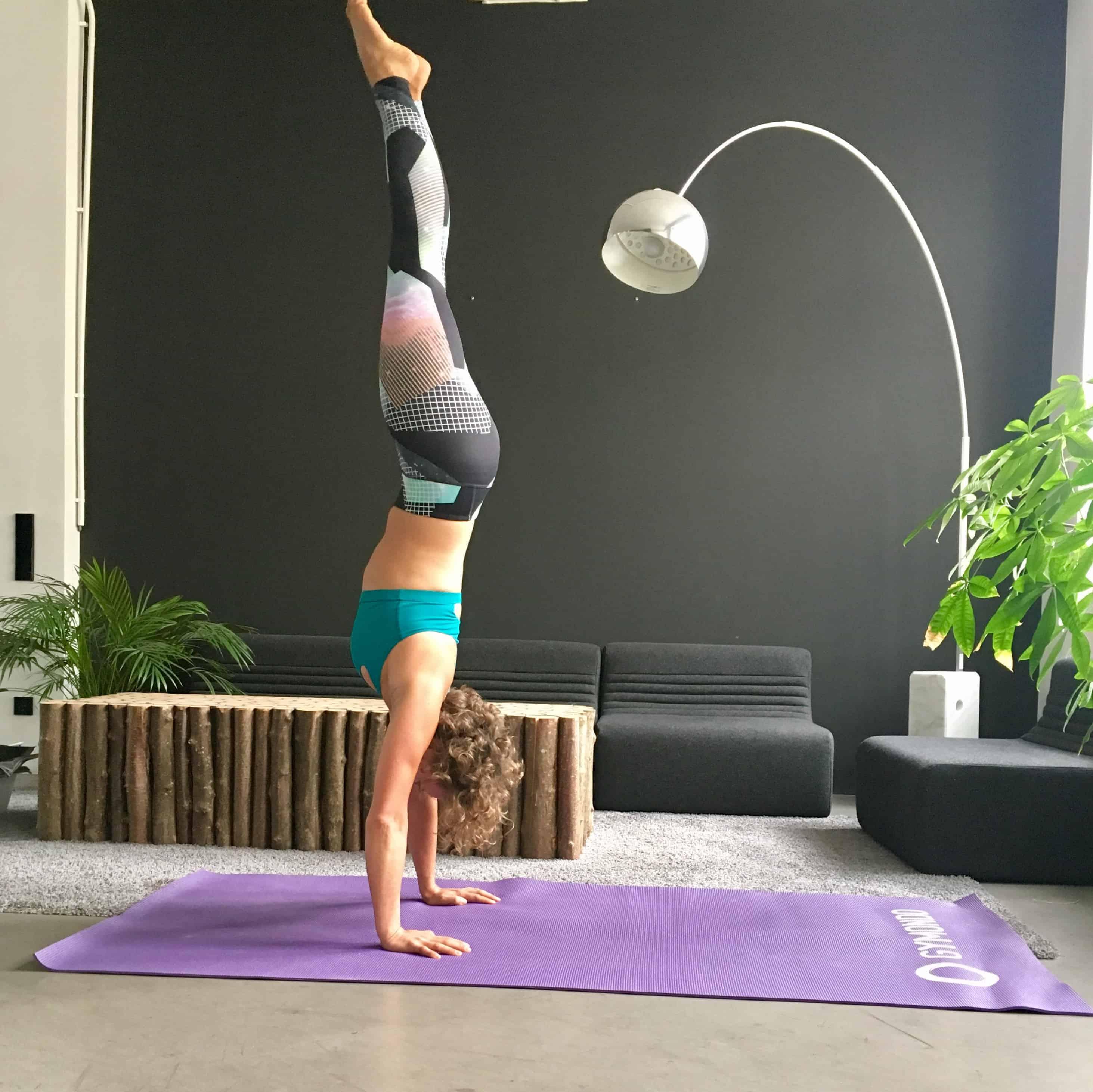 Frau macht Handstand auf lila trainingsmatte