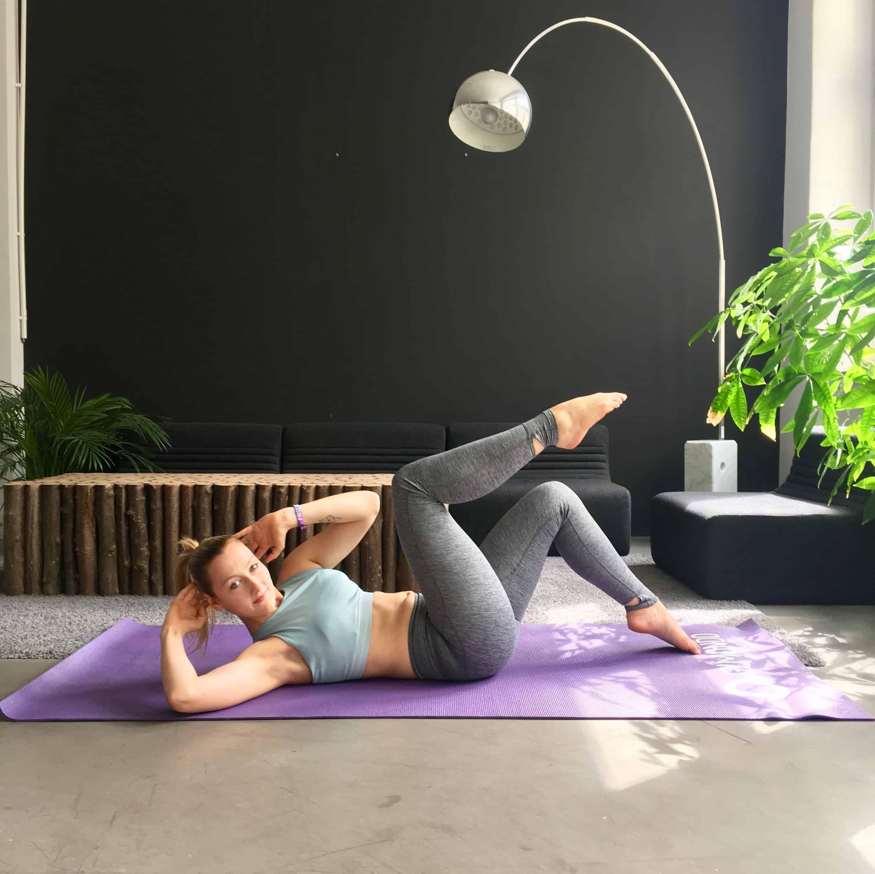 Frau macht Diagonale Crunches auf lila trainingsmatte