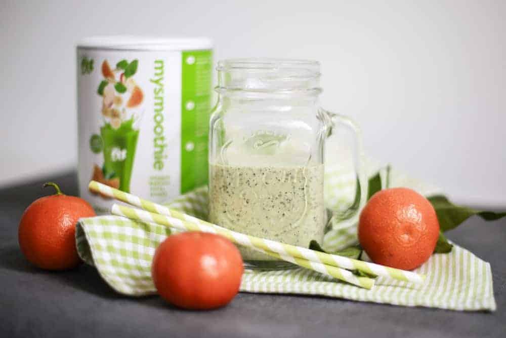 Grüner Smoothie in Glas auf Tisch dekoriert mit mysmoothie Flakes und Mandarinen