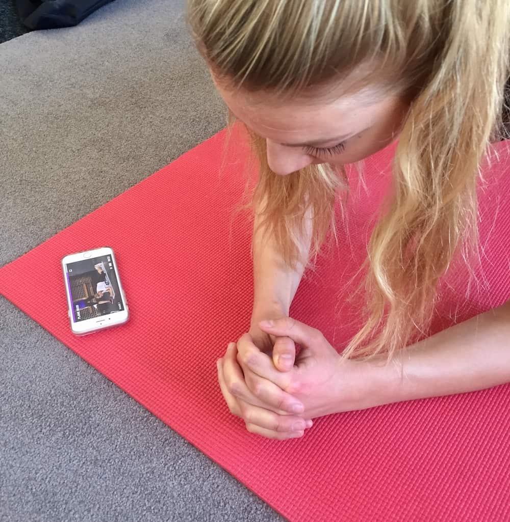 Junge Frau trainiert zu Hause auf roter Trainingsmatte. Weißes Smartphone liegt vor ihr. Gymondo Erfahrungen