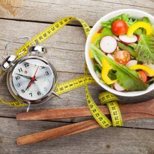 Eine Uhr, ein Maßband und eine Schale Salat verdeutlichen, dass man bei Intervall Fasten nur zu bestimmten Uhrzeiten isst, um Abzunehmen