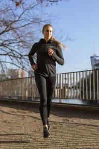 Frau beim Lauftraining in Laufkleidung joggt am Wasser.