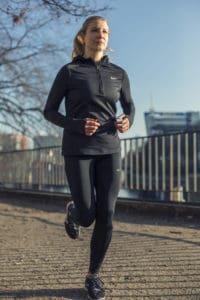 Junge Frau in schwarzer Sportkleidung joggt durch den Park