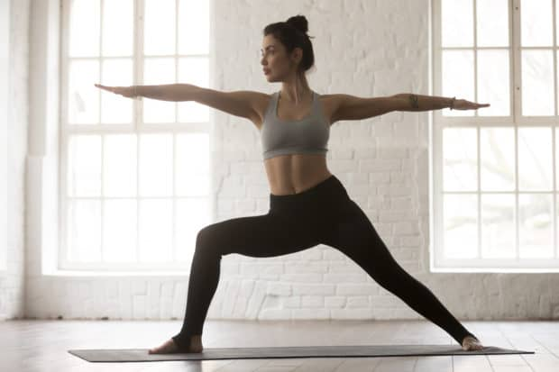 Junge Frau macht Yoga Krieger 2