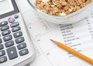 Kalorienzählen mit Taschenrechner, daneben Müslischale