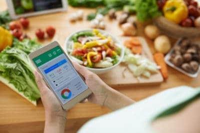 Frau hat Smartphone in den Händen mit App zum Kalorienzählen, in Hintergrund bunte Lebensmittel auf Holztisch