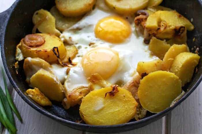 Bratkartoffeln mit Spiegeleiern in der Pfanne
