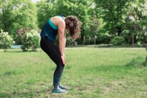 Junge Frau auf einer Raststätte macht Übung Rückenstretch