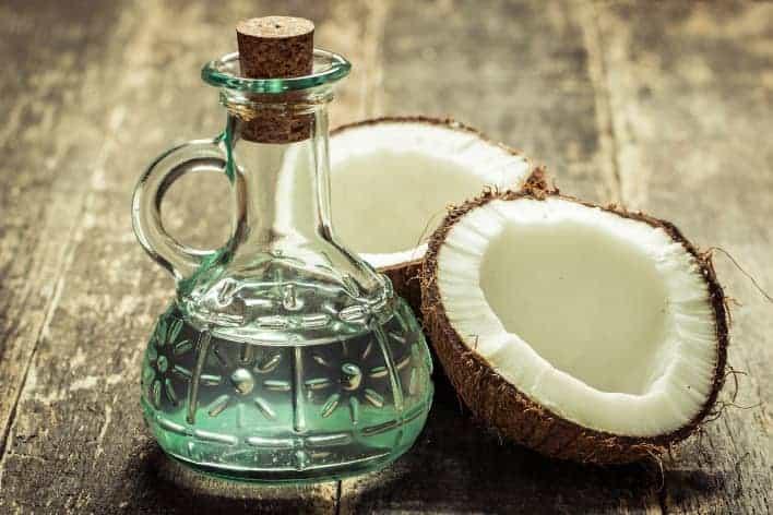 kokosnussoel in Glaskaraffe mit aufgeschlagener Kokosnuss auf Holztisch