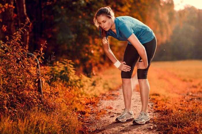 Frau beim Joggen stützt sich erschöpft mit den Händen auf den Knien ab