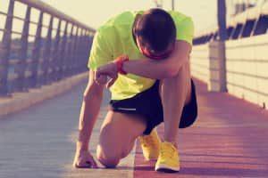 erschöpfter Sportler auf Brücke.