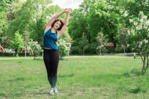 Junge Frau auf einer Raststätte macht Übung Lat Stretch